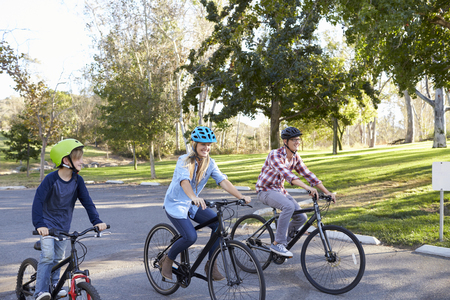 Parents and young son cycling together through a park photo