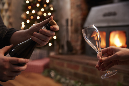 yule log: Couple Opening Champagne In Room Decorated For Christmas