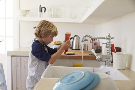 household chores: Boy squeezing washing up liquid into sink to wash dishes