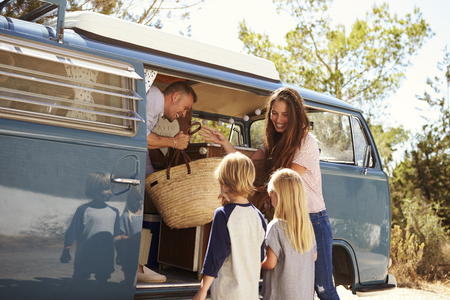 family vacation: Family packing up their camper van for a road trip vacation Stock Photo