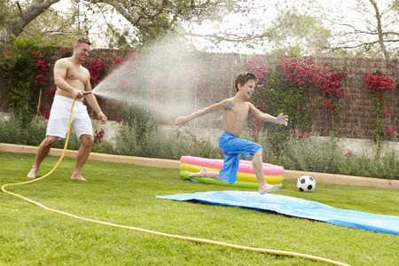 Father Spraying Son With Garden Hose Stok Fotoğraf