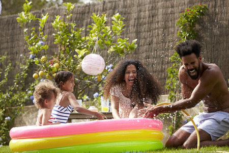 Family Having Fun In Garden Paddling Pool Stock Photo - 71404773