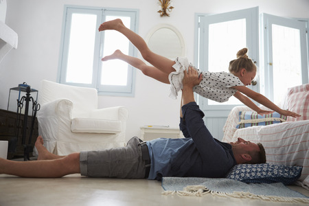 Father Lifting Daughter Into The Air Indoors 스톡 콘텐츠