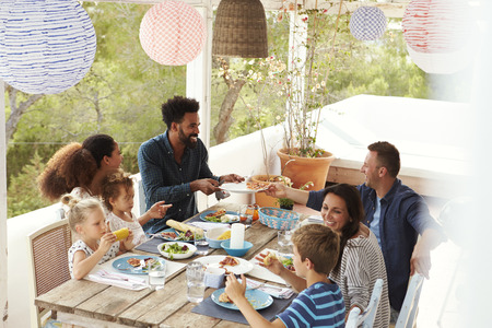 families together: Families Enjoying Outdoor Meal On Terrace Together
