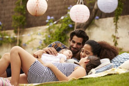 En famille avec bébé détente sur Rug In Garden Together