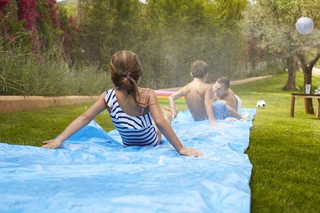 Rear View Of Family Having Fun On Water Slide In Garden Stock Photo