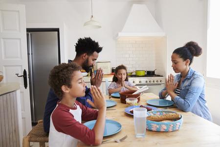 familia orando: Familia diciendo gracia en la mesa de la cocina antes de su comida