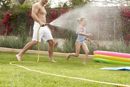 Father Spraying Daughter With Garden Hose