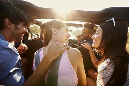 Cinco amigos que viajan juntos en un viaje por carretera en un coche Foto de archivo - 71404618