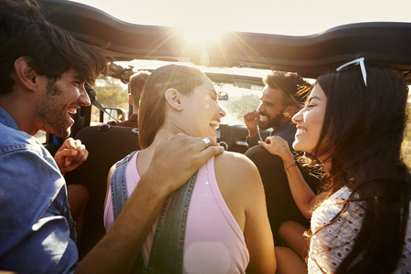 Five friends travelling together on a road trip in a car Imagens - 71404618