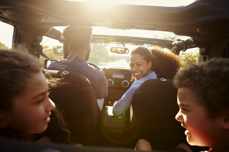 Happy family on a road trip in their car, rear passenger POV Stockfoto