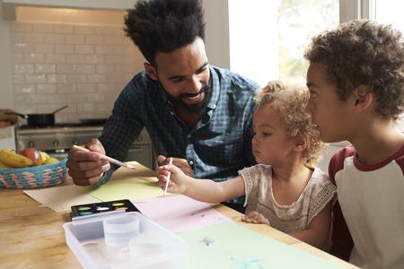 子供と父は台所のテーブルに絵を描いて