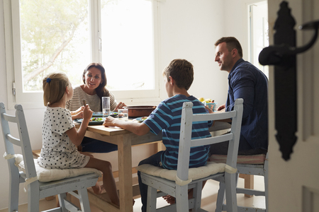 Family At Home In Eating Meal Together Stock Photo