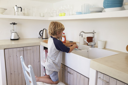 wash dishes: Young boy kneeling on a chair to wash dishes, full length