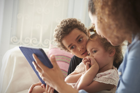 Mother And Children Sitting On Sofa Using Digital Tablet Stock Photo