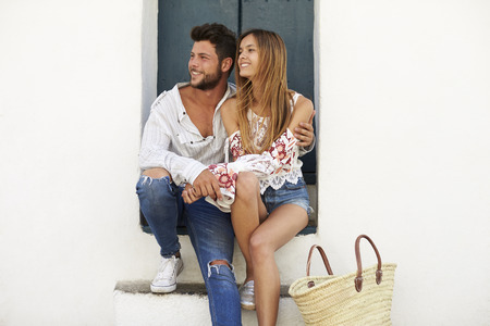 Happy couple sitting in a doorway looking away, Ibiza, Spain Stock Photo