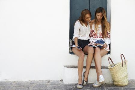 Female friends sitting in doorway reading a guidebook, Ibiza