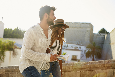 three day beard: Young adult couple sightseeing in Ibiza, Spain, side view Stock Photo