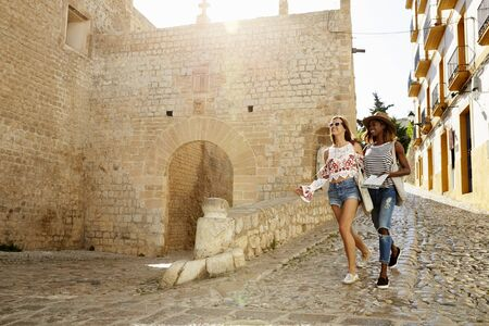 travel woman: Two female friends on holiday walking with guidebook, Ibiza