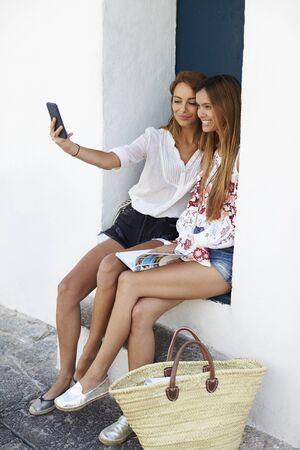 Female friends sitting in doorway taking a selfie, Ibiza