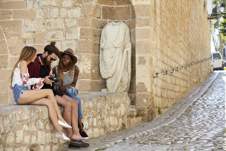 three day beard: Friends sit on a wall looking at photos on a camera, Ibiza Stock Photo