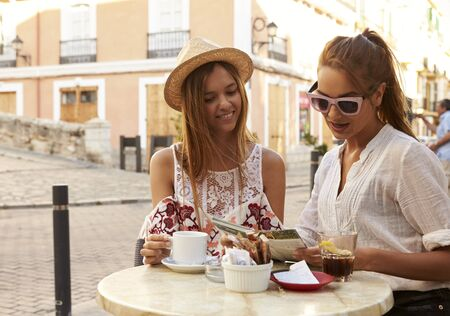 incidental people: Two female friends reading a guidebook outside a cafe, Ibiza Stock Photo