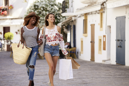 Two female friends on vacation shopping in Ibiza, front view Stock Photo