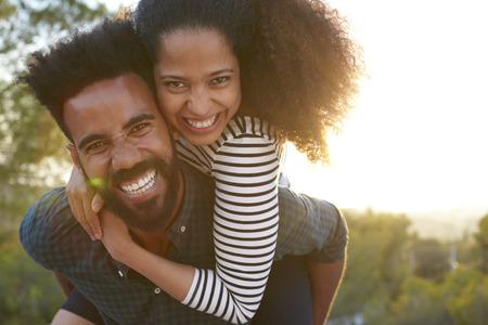 Man die jonge vrouw op zijn schouders, op zoek naar camera Stockfoto