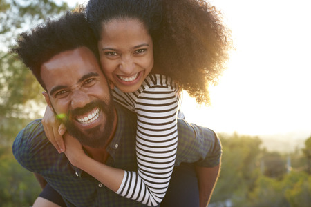 Mann mit jungen Frau auf den Schultern, Blick auf Kamera