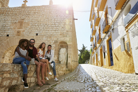 thai ethnicity: Friends on holiday in Ibiza sit on a wall looking to camera