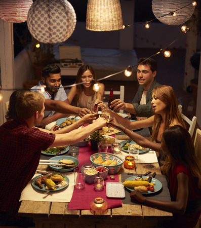 Friends making a toast at a patio dinner party, vertical Standard-Bild