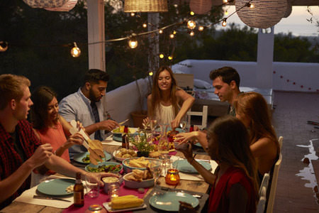 Friends talking at a dinner party on a patio, elevated view Stock Photo