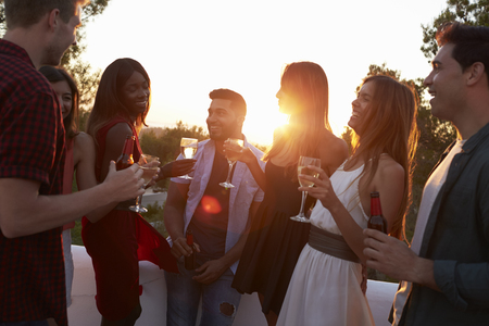 flare up: Adult friends socialising at a party on a rooftop at sunset Stock Photo