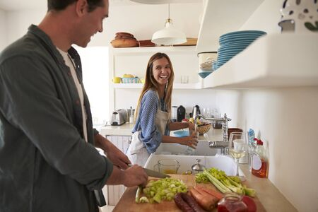 each: Young adult couple  preparing food look at each other