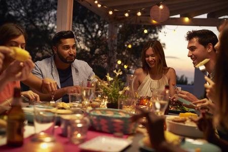 Des amis mangent et parlent lors d'un dîner sur une terrasse, de près Banque d'images - 71404108