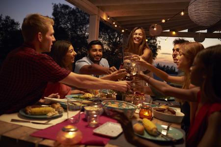 anochecer: Los amigos hacen un brindis en una cena en un patio, de cerca