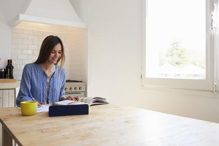 Vrouw met boek en tablet computer schriftelijk op de keuken tafel