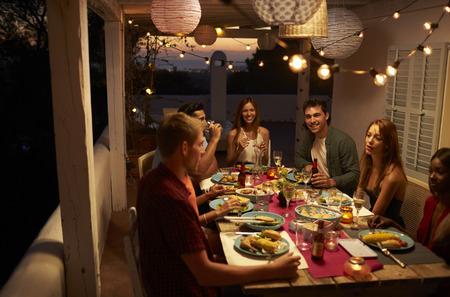Vrienden die bij een dinerpartij op een terras, Ibiza, Spanje spreken Stockfoto