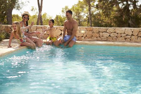Weitwinkelansicht der Familie im Urlaub, die Spaß durch Pool