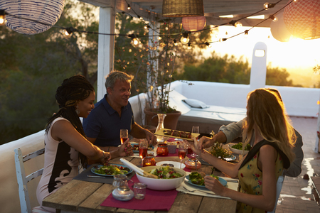 eating dinner: Two couples eating dinner at sunset on a rooftop terrace