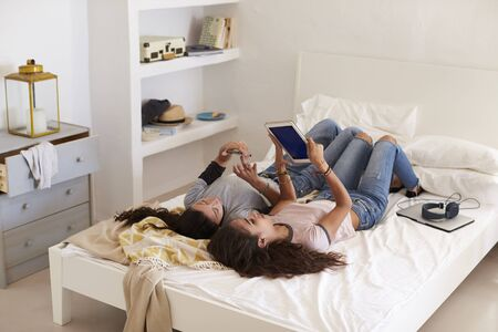 girl with laptop: Two girls lying on bed using phone and tablet, elevated view
