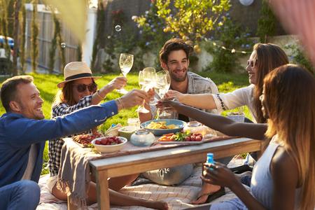 tomando vino: Grupo de amigos que disfrutan al aire libre de la comida campestre en jardín
