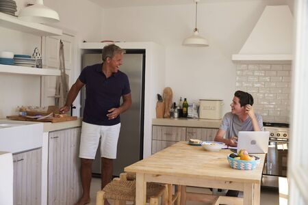resting: Happy father talking to his son, doing homework in kitchen