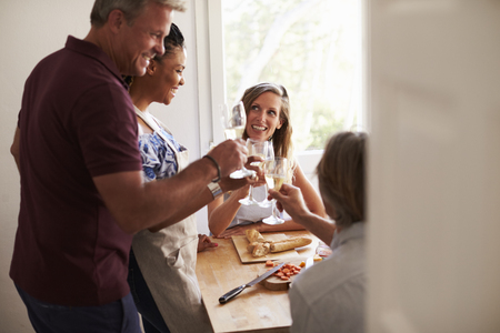 dinner party: Couples make a toast while preparing food, view from doorway