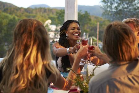 Koppels roosteren tijdens het avondeten op een terras, over schouderzicht Stockfoto - 71403646