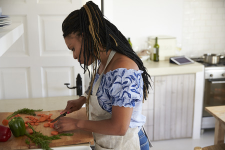 Woman standing in kitchen chopping vegetables