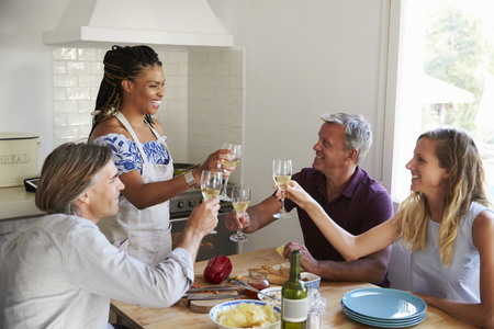 turning table: Two couples preparing dinner make a toast at kitchen table