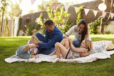 tickling: Parents Playing Game With Children On Blanket In Garden
