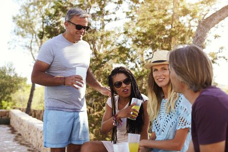 couples outdoors: Two adult couples socialising outdoors, Ibiza, close up Stock Photo
