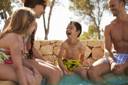 family vacation: Family On Vacation Relaxing By Outdoor Pool